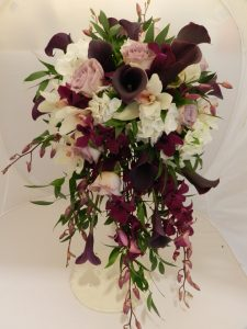 A stunning cascade bouquet in aubergine, lilac and white